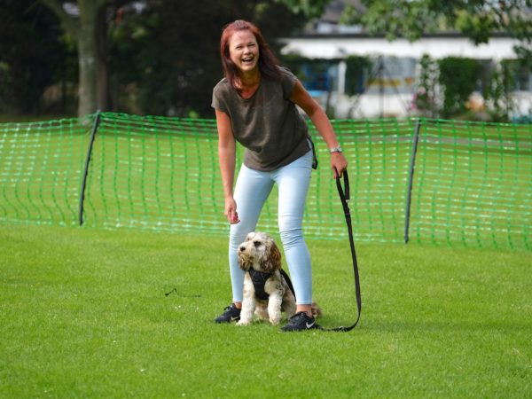 lady enjoying and laughing with dog in middle game
